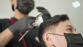 Barber using scissor trimming Asian male customer. close up face guy get a Hair Cut at the Barbershop wear black protective mask. job opportunity, start up business, Pandemic Covid-19 re-open business