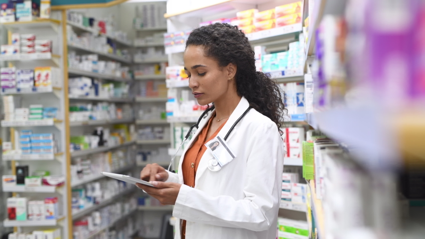 Happy friendly multiethnic pharmacist doing inventory in a provided and modern pharmacy while looking at camera. Portrait african smiling young doctor woman working in drugstore with digital tablet. Royalty-Free Stock Footage #1056031163