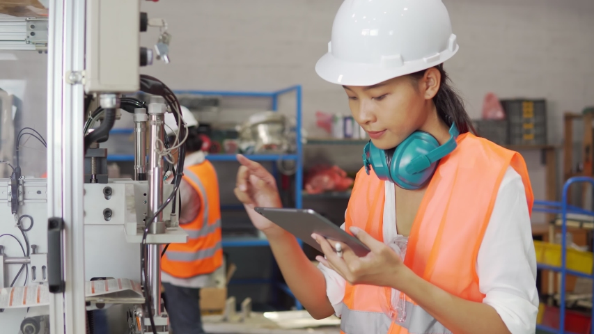 Footage B-roll of Female factory worker technician check a machine. Business Women engineering holding tablet check product quality. Smart Technology. Industrial working concept. Business industrial | Shutterstock HD Video #1056031202