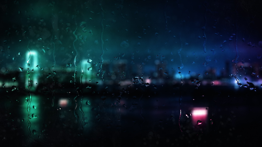 Beautiful cinematic rainy city window backdrop A rain covered window with blurry city lights bokeh background and raindrops running down the glass