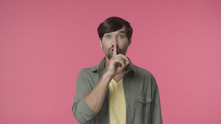Handsome bearded man asking keep promise and secret safe, shushing with finger pressed to lips, make hush shh sign to tell be quiet or silent, dont speak its taboo, pink background | Shutterstock HD Video #1056037190