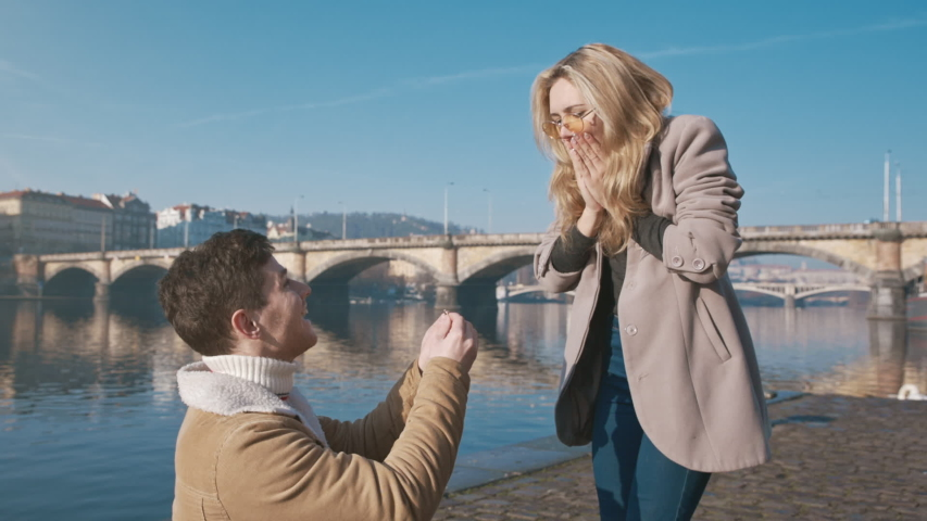 Happy woman taking a proposal about wedding and kissing her future husband. Handsome young man giving an engagement ring to her girlfriend. Couple dating on the bridge. Concept of love and marriage. Royalty-Free Stock Footage #1056045440
