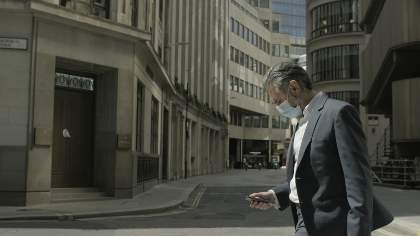 Corporate business man commuting to work wearing face mask and using smart phone in the city of London during Covid-19 Pandemic Royalty-Free Stock Footage #1056046832