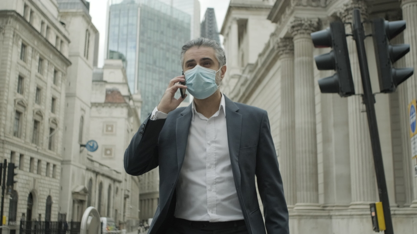 Corporate business man commuting to work wearing face mask in the city of London during Covid-19 Pandemic Royalty-Free Stock Footage #1056048392