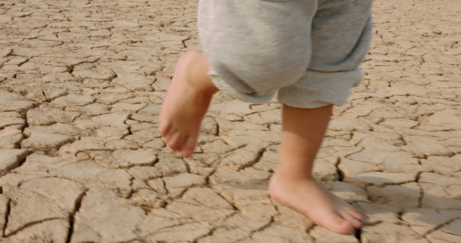Close up shot of legs of baby boy running on cracked soil, destroyed by overuse, climate change and flood - ecological issues, save our planet 4k footage Royalty-Free Stock Footage #1056048947