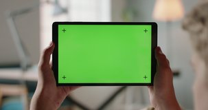 Close up shot of hands holding a tablet computer with green mock up screen. A template for video conference or online store 4k footage