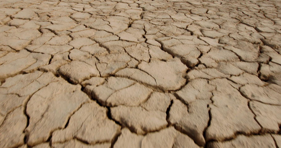 Dynamic shot of cracked soil ground of dried lake or river in mountains. Land destroyed by erosion and global warming - ecological issues concept 4k footage Royalty-Free Stock Footage #1056048971