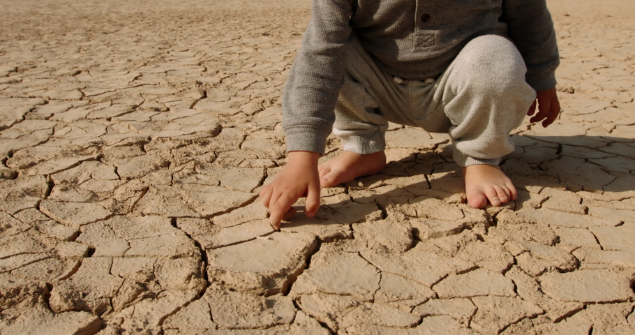 Close up shot of baby boy poking pieces of dry cracked mud. Cracked soil ground of dried lake or river destroyed by global warming - ecological issues  Royalty-Free Stock Footage #1056048974