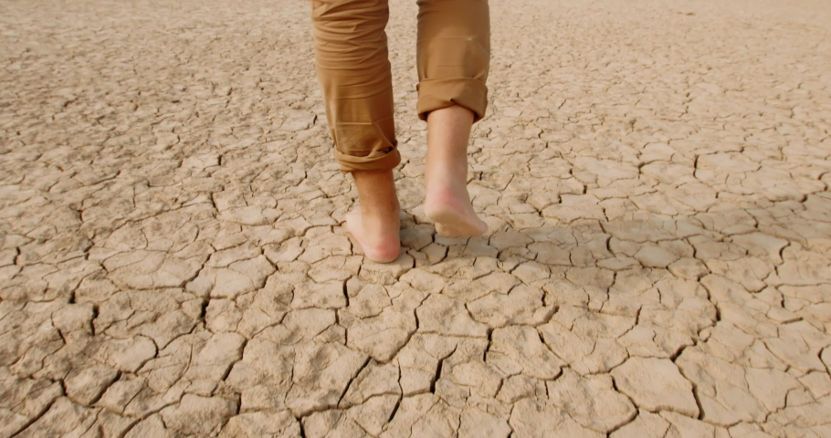 Close up shot of feet of adult man walking barefoot on bottom of dried lake or river, stepping on cracked soil ground destroyed by erosions - ecological issues concept  Royalty-Free Stock Footage #1056048977