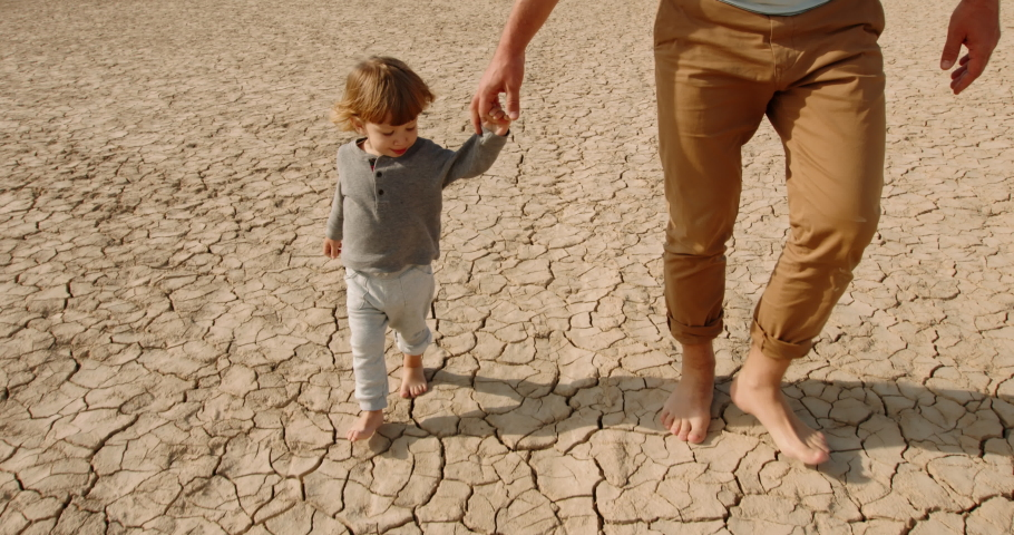 Caucasian baby boy with his father walking barefoot on bottom of dried lake or river, stepping on cracked mud destroyed by global warming - ecological issues concept 4k footage Royalty-Free Stock Footage #1056048980