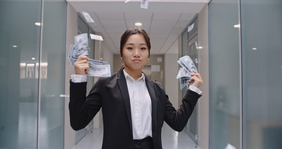Successful asian manager in formal suit standing in office hall, throwing money in the air, celebrating her victory- way to success concept 4k