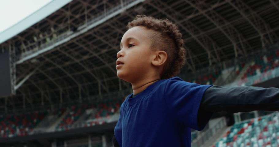 Portrait of cute little black kid boy spreading hands on a large football stadium, dreaming of becoming professional player, soccer star. Shot on RED camera with anamorphic lens Royalty-Free Stock Footage #1056050417