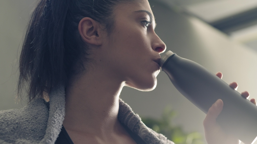 fitness girl drinking from sport bottle during a workout pause at home or gym. Close backlit portrait of active woman drinking from water bottle while resting from training Royalty-Free Stock Footage #1056051659