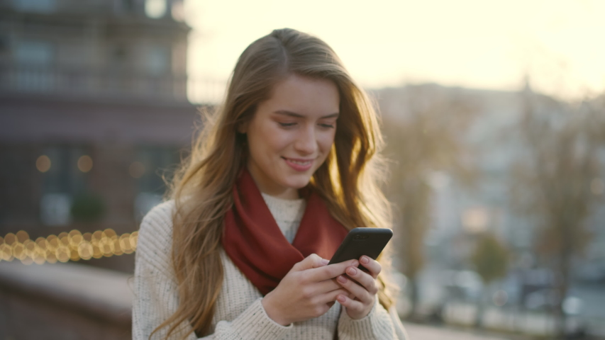 Portrait of happy hipster woman typing by mobile phone outdoors. Closeup cheerful girl walking with smartphone in urban background. Smiling lady holding cellphone in hands outside. Royalty-Free Stock Footage #1056052220