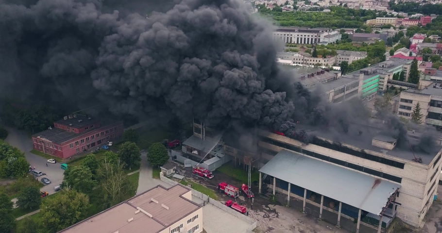 Aerial View of Firefigters Extinguishing a Large City Building Caught on Fire. Top View of a City District Covered in Dense Clouds of Black Rolling Smoke Rising from the Strongly Burning Old Royalty-Free Stock Footage #1056053306