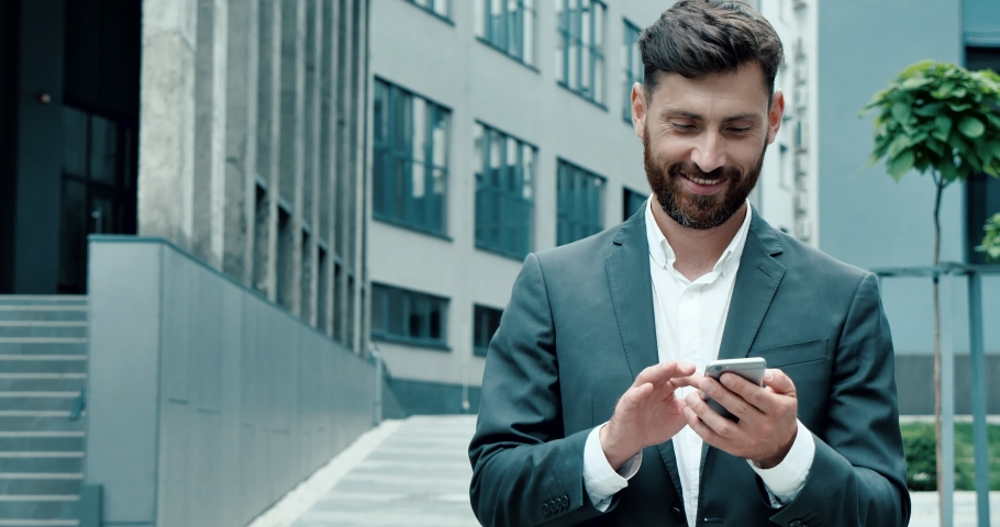 Successful happy Businessman in Luxury grey Suit is texting Messages on his modern Smartphone. Young Man is walking in Business Quartal, having good Mood, looking Satisfied. Successful Lifestyle. Men.