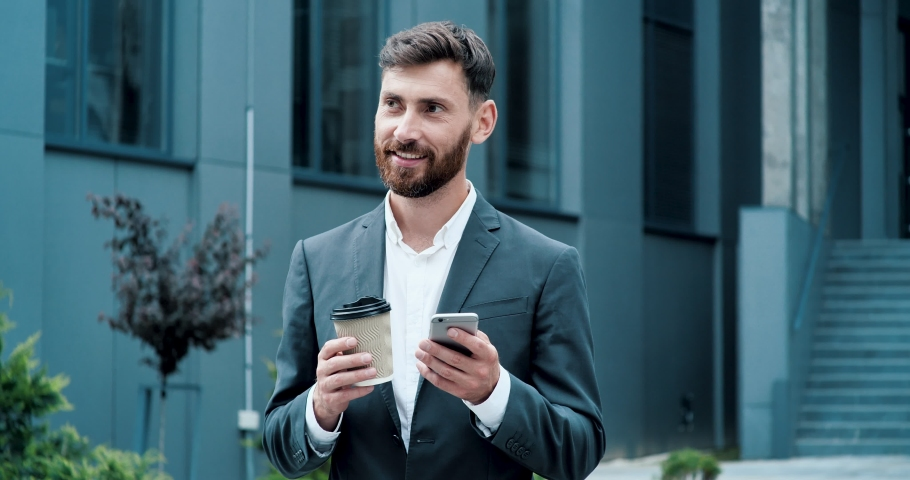 Dark Haired Attractive Business Man with a Beard typing something on his Smartphone, drinking Coffee to go. Concentrated Business Man Reading something in his Phone with cute Smile. Success. Phones. Royalty-Free Stock Footage #1056058487