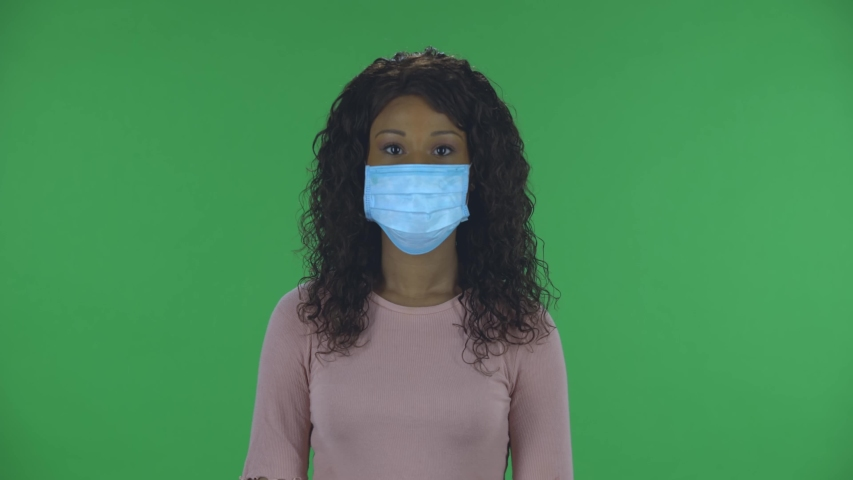 Portrait of beautiful african american young woman in medical mask is looking straight. Burning brunette with wavy hair in jeans and a beige blouse on a green screen in the studio. Health Protection