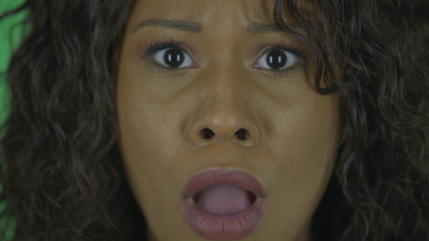 Portrait of beautiful african american young woman is looking at camera scared and says wow with shocked facial expression. Burning brunette with wavy hair in jeans and a beige blouse. Close up. Macro