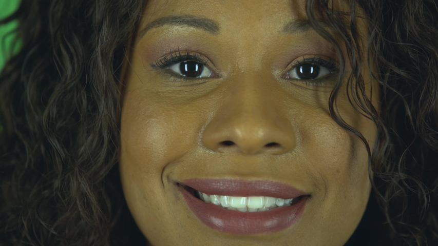 Portrait of beautiful african american young woman is looking seriously at the camera and then smiling revealing teeth. Burning brunette with wavy hair in jeans and a beige blouse. Close up. Macro