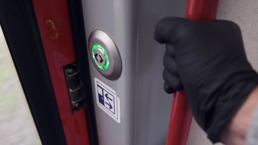 POV, Hand in protective medical gloves push Green button to open automatic door on the train. COVID-19 public transport as Infection pathway. Detail shot of a train door button | Shutterstock HD Video #1056068183