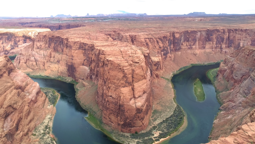 World famous tourists attraction - Horseshoe bend on a cloudy day. Cinematic American Wild West wilderness nature. Aerial red canyon and Colorado river. USA travel and road trip concept footage   Shutterstock HD Video #1056068294