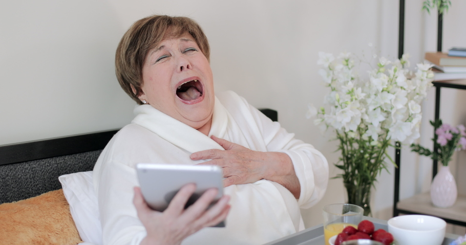 Elderly woman in home rob laughing while looking at screen of her modern gadget. Old female retiree in good mood watching funny video while using tablet and having breakfast in bed