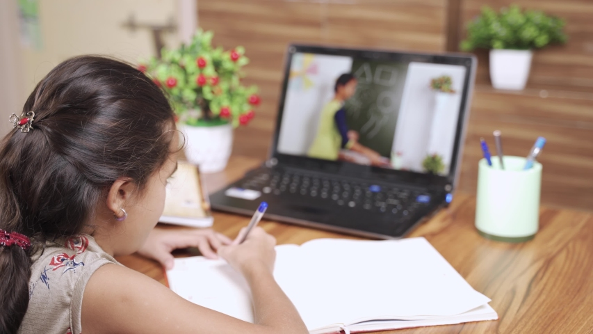 teenager girl busy in writing or learning drawing by looking to the laptop during coronavirus homeschooling - concept of kids e-learning, virtual class during covid-19 pandemic. Royalty-Free Stock Footage #1056070631
