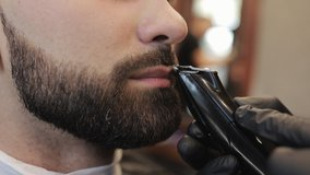 Barber shaving bearded man in barbershop. Male skin care and beard style concept. Master hairdresser with a professional trimmer in a black gloves makes a haircut and evens the beard to a customer.