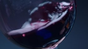 Waving red wine in a glass on defocused background . Beautiful stock footage for wine commercial . Close up video of wine mixing process inside goblet . Shot on ARRI ALEXA Camera in Slow Motion .