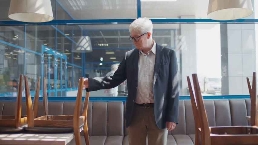 Sad senior small business owner walking in empty cafe closed because of quarantine. Mature unhappy entrepreneur bankrupt in closed restaurant. Small business crisis during quarantine concept Royalty-Free Stock Footage #1056077492