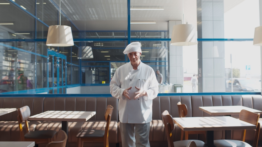 Portrait of senior chef in white uniform walking in empty cafe waiting for customers. Restaurant chef checking cleanliness of furniture before opening. Small business concept | Shutterstock HD Video #1056077498