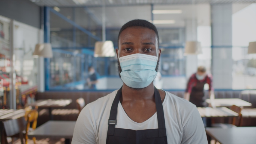 Portrait of afro-american waiter wearing protective mask looking at camera over blurred background of cafe interior. Young african coffee shop owner or barista in apron and safety mask Royalty-Free Stock Footage #1056077531