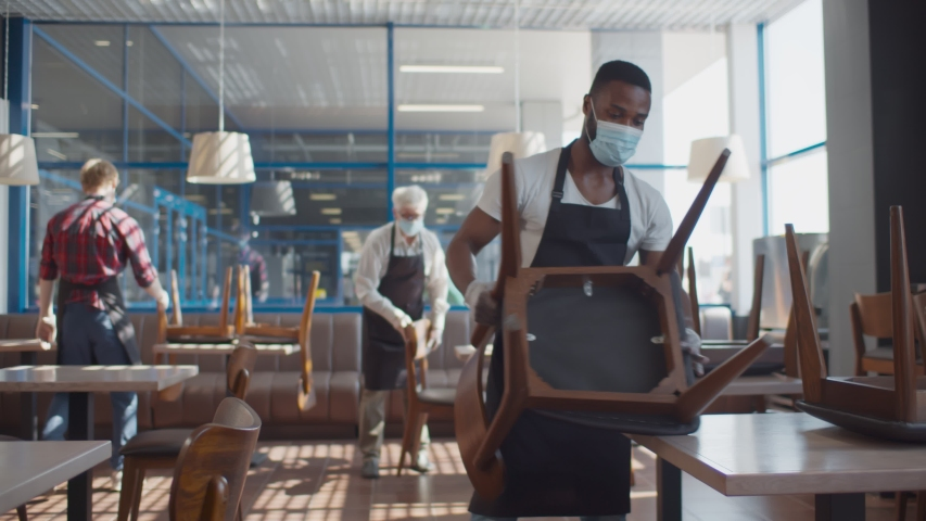 Multiethnic staff in facial masks preparing restaurant for reopening after quarantine. Young waiters in aprons protective masks and gloves arranging furniture in cafe before open | Shutterstock HD Video #1056077573