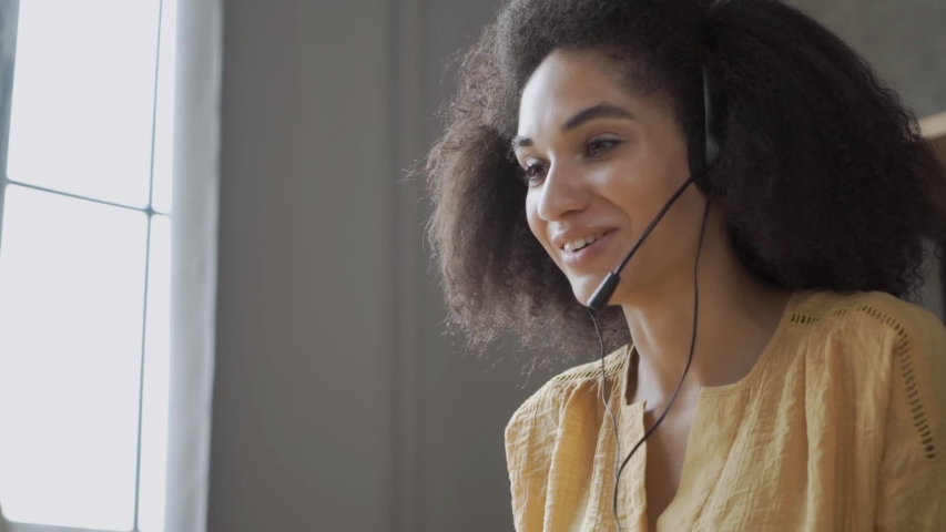 Smiling African American woman with headset using laptop, talking, working customer support service operator at home \office, in headphones with microphone