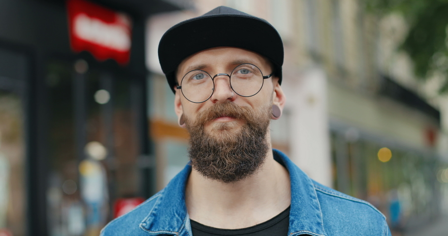 Camera zooming in male face with beard and in glasses outdoors. Portrait of young handsome Caucasian guy hipster in hat and with ears tunnels smiling joyfully at street. Close up of stylish man. | Shutterstock HD Video #1056081941