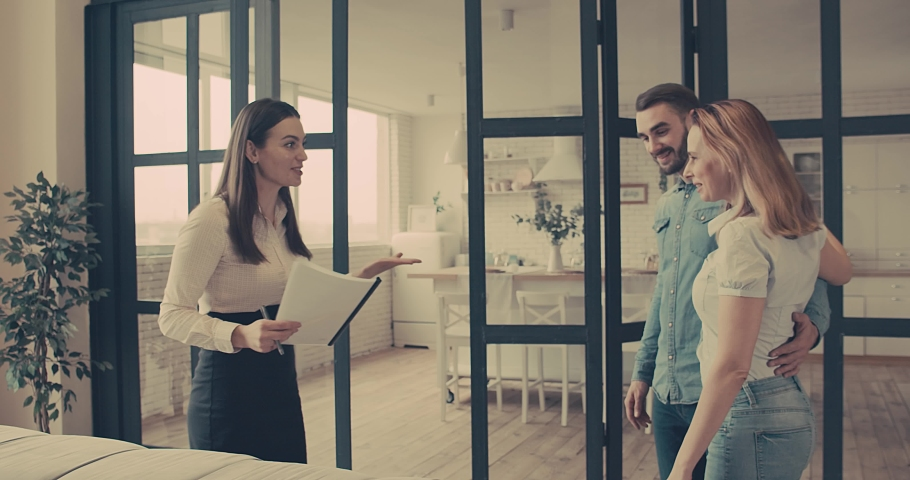Happy Couple with real-estate agent visiting house for sale or for rent, Young man and woman cheerful at home. Loving people buying an apartment. Immovables market 4K slow motion video. Royalty-Free Stock Footage #1056082493