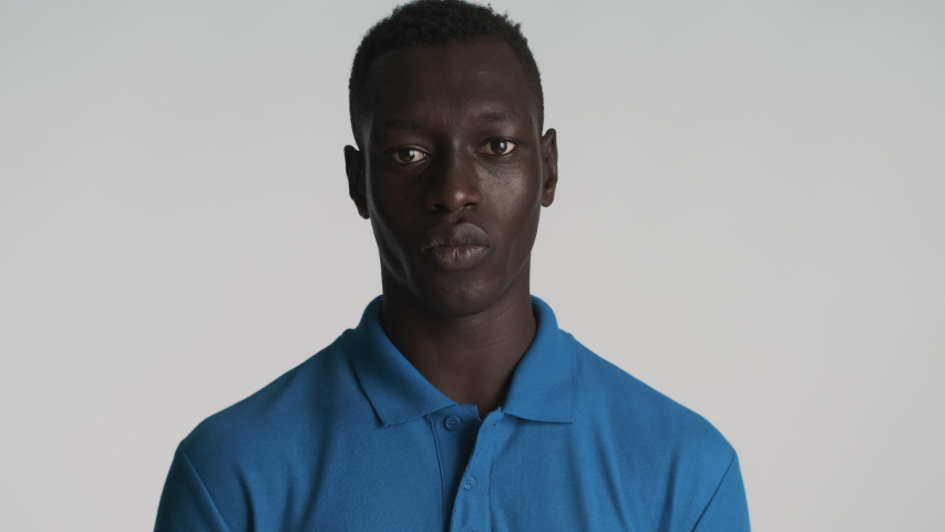 Young attractive African American man confidently showing silence gesture on camera over gray background. Shh expression | Shutterstock HD Video #1056083834