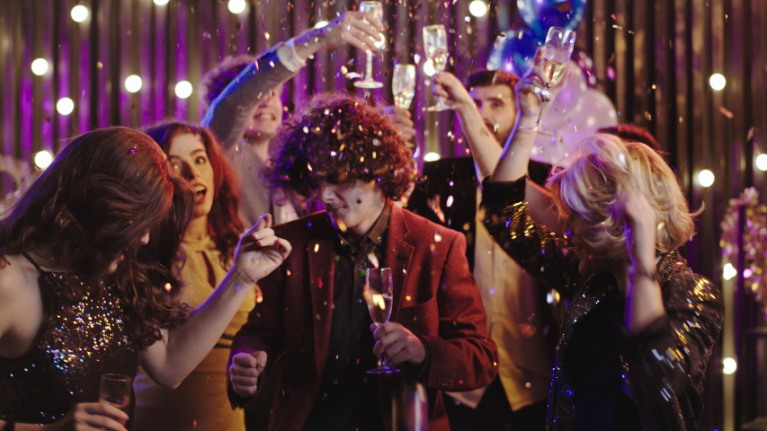 Happy and excited group of colleagues at at Christmas stuff party dancing drinking champagne and enjoying the party very hard Royalty-Free Stock Footage #1056085370