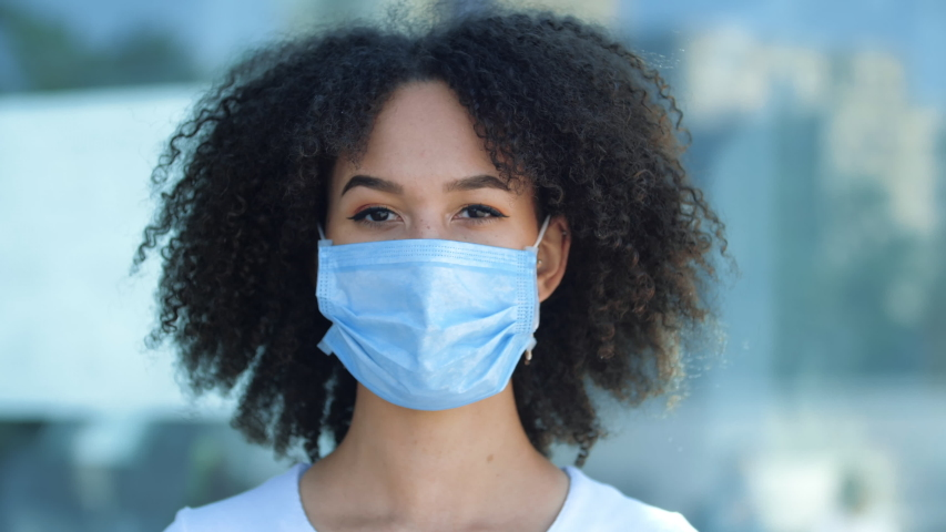 Beautiful smiling young African woman shows with two fingers wearing mask to protect against outbreak of coronavirus during second wave of pandemic. Ethnic female student showing thumbs up, close up Royalty-Free Stock Footage #1056085715