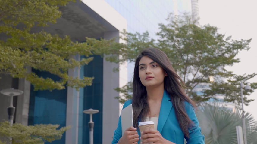 A confident corporate/ office woman employee in formal dress holding a coffee mug and laptop in hands walking along the street. An attractive and beautiful businesswoman outside commercial complex.