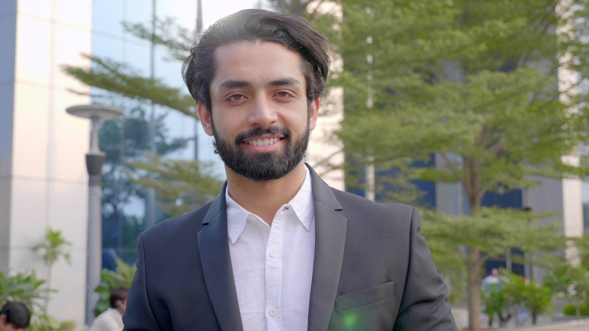 A well dressed happy bearded office/ corporate male executive standing outside a modern corporate building. A handsome businessman smiling and looking into the camera outside modern commercial complex Royalty-Free Stock Footage #1056089255