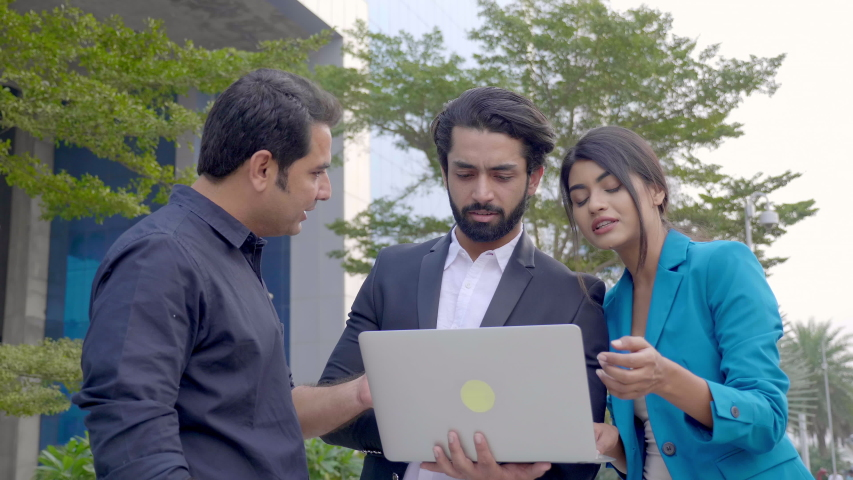 A team of business partners are standing outdoors and discussing an upcoming project using laptop. A group of male and female corporate office employees are interacting outside commercial complex  Royalty-Free Stock Footage #1056089258