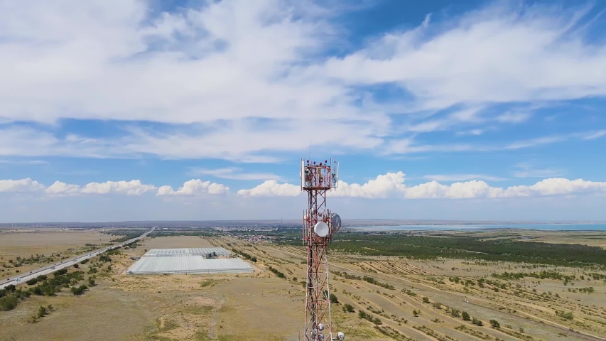 Aerial footage around a telecommunications tower with sector antennas of a mobile operator and radio relay equipment in the city. Telecommunication equipment in Kazakhstan. 5G technology. Telecom | Shutterstock HD Video #1056089960