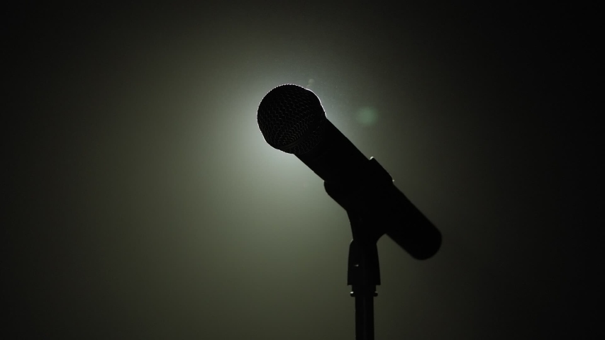 Close-up of microphone on stage against a black background with white lighting and smoke. The silhouette of the microphone in the dark. Music instrument concept. Royalty-Free Stock Footage #1056091373