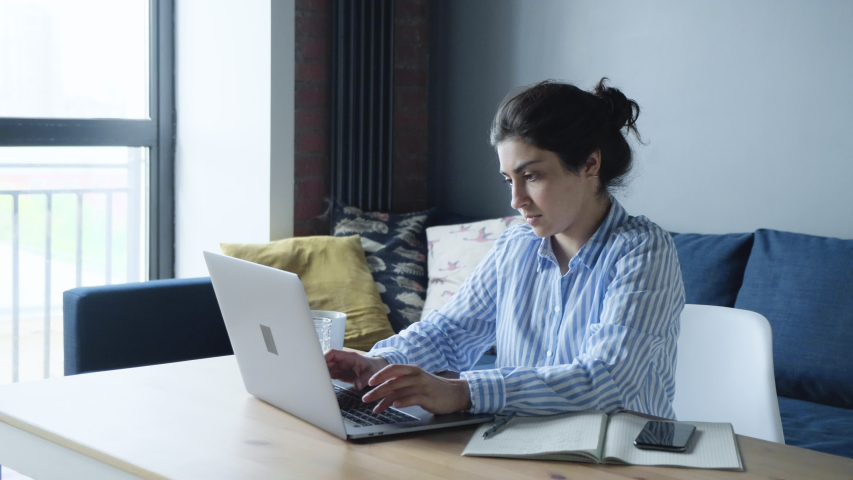 Concentrated Millennial Indian Female College Student Woman Doing University Assignment. Royalty-Free Stock Footage #1056093599