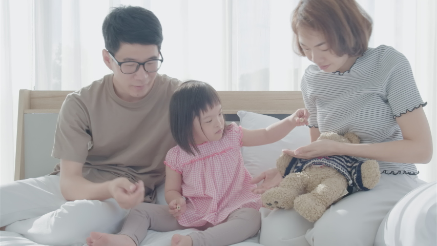 Children and parents in bed. Parents are playing with children on the bed. Children are laughing because of parents. A happy family smiled at the bed in the morning.