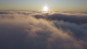 Amazing aerial shot of heavenly golden clouds in the sky. Cinematic 4K of sun shining above the clouds with beautiful beams and lens flare. Drone flying through beautiful sunny cloudscape at sunrise