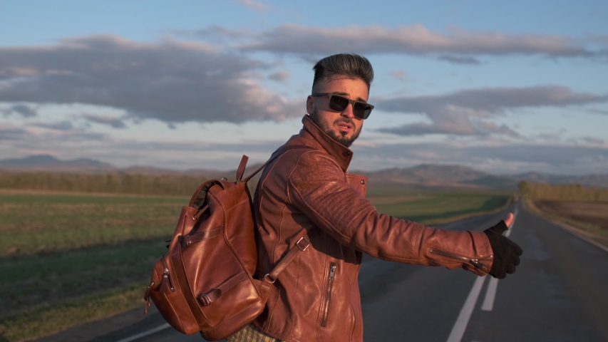 Hipster hitchhiker tourist traveler man with backpack walking along long road, hitchhiking lifting thumb up in summer to stop car. trip hitching mountain nature travel tourism adventure, 4 K slow-mo