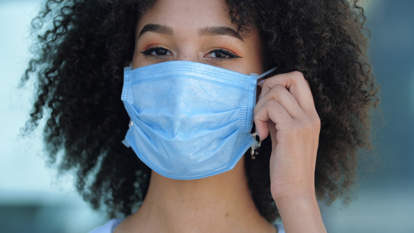 African ethnic woman takes off her protective mask, smiles, breaths in deeply, rejoices at end of flu epidemic. Foreign student gets freedom of movement world feeling relief after quarantine ends
